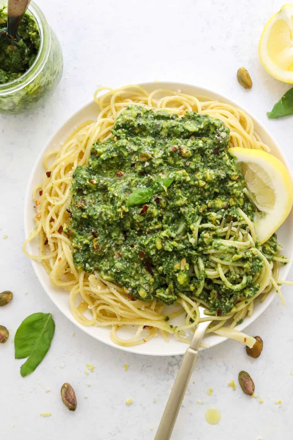 Round plate of spaghetti topped with chunky homemade basil pesto recipe with a jar of the pesto behind it and sliced lemon next to it