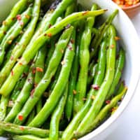 Easy green beans on a kitchen towel with red pepper flakes