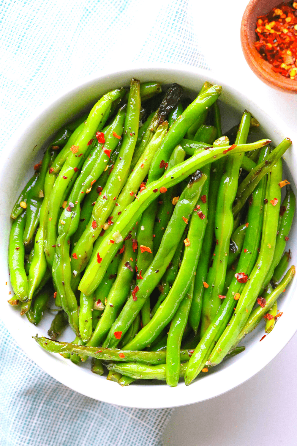 string green beans in a round bowl with red pepper flakes on top