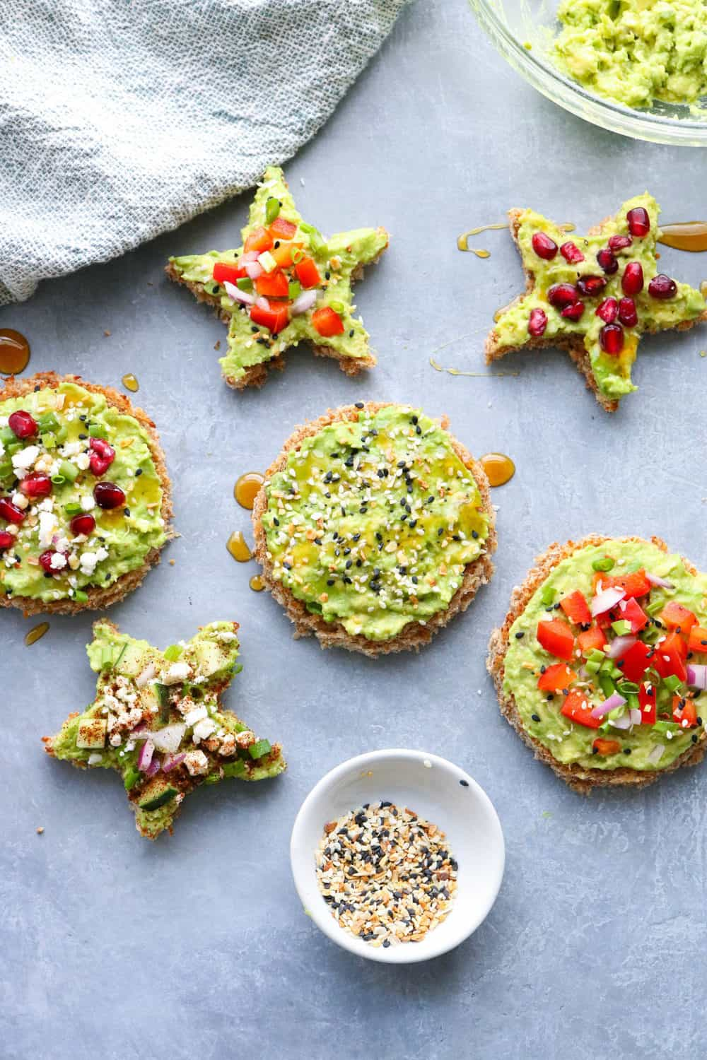 circle and star shapped avocado toast topped with peppers, cheese, and pomagrantes