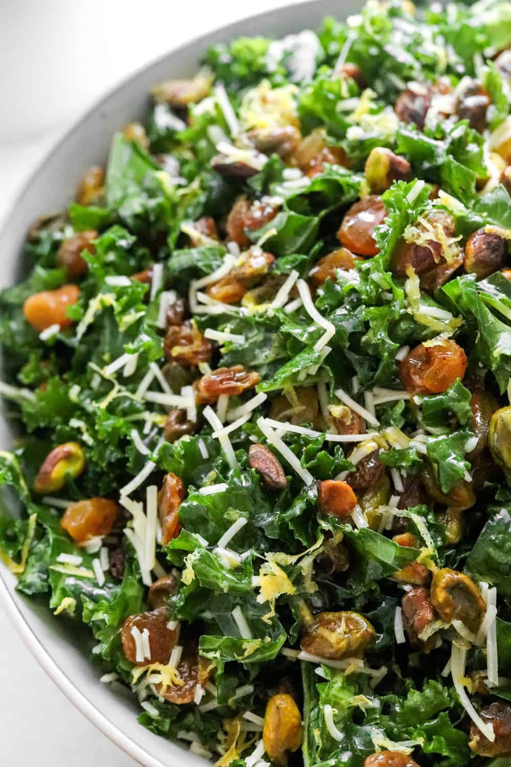 close up of shredded kale with nuts and raisins mixed into it and shredded cheese on top of it in a round white bowl