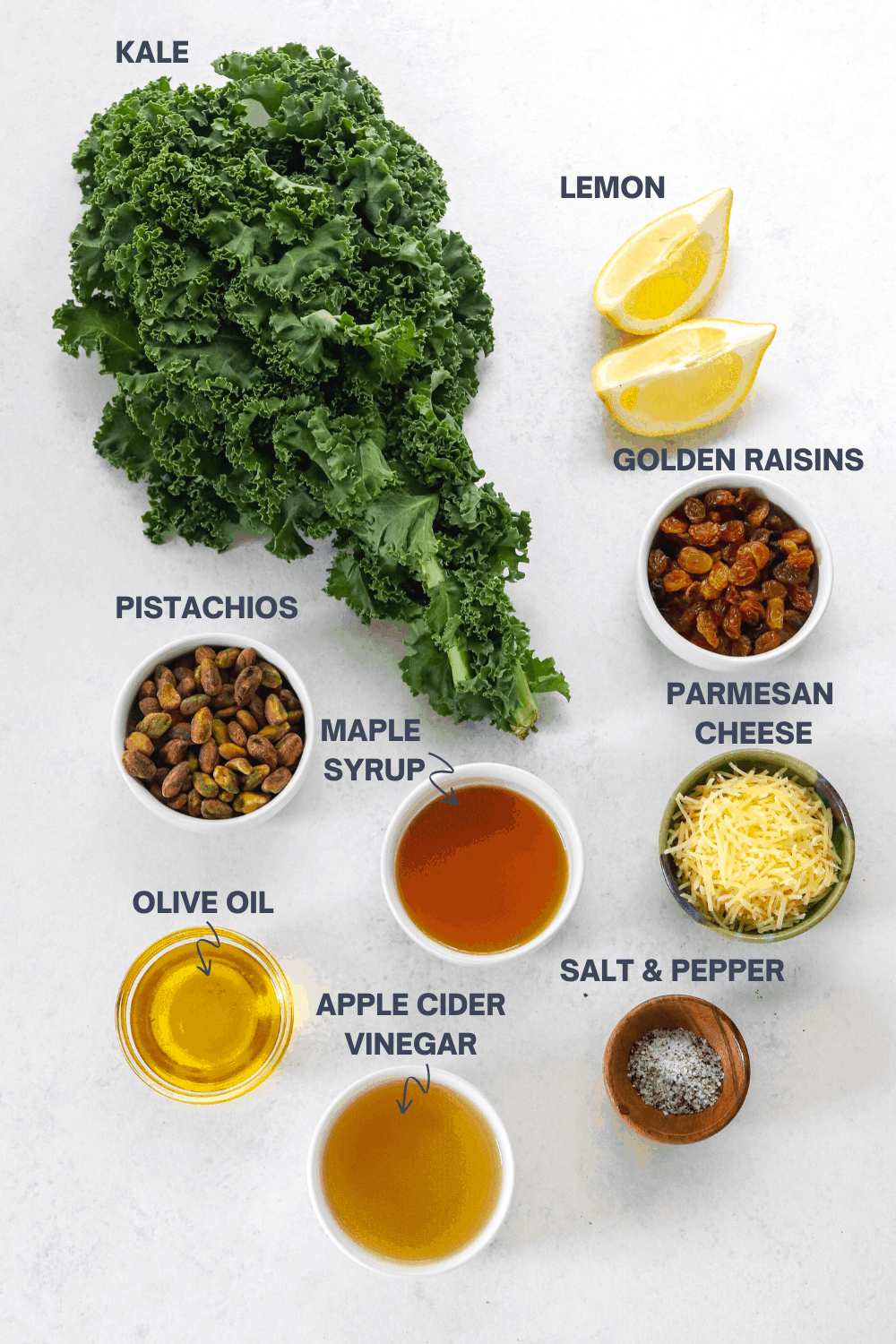 Bunch of kale, sliced lemons, bowl of shelled pistachios, golden raisins, parmesan cheese, olive oil, vinegar and maple syrup on a white surface with labels for each ingredients