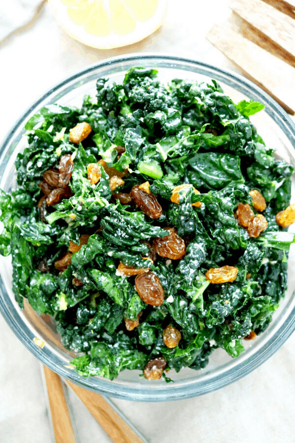 Sliced green kale in a mixing bowl with golden raisins