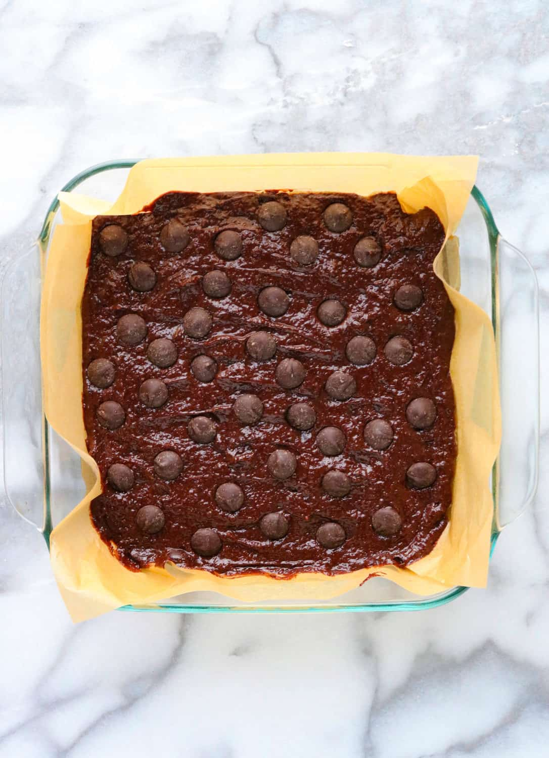 brownie batter in a glass dish topped with chocolate chips