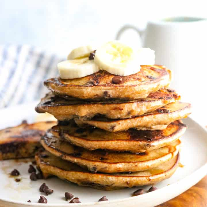 Close up of stack of pancakes with banana on top
