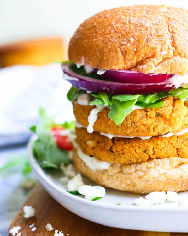 Chickpea Cauliflower Burger on a bun with tomato and onions stacked on a white plate