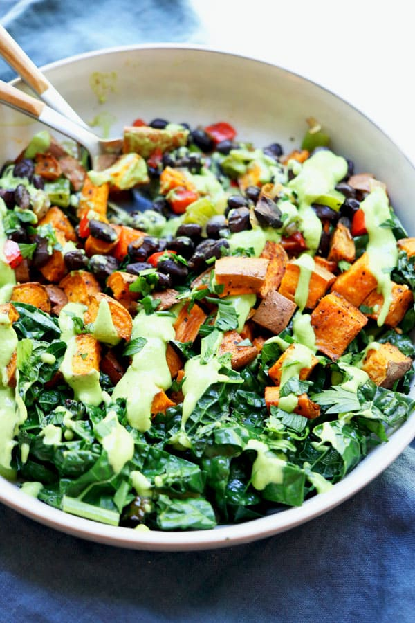 cooked kale, black beans and roasted sweet potato in a bowl topped with  avocado sauce