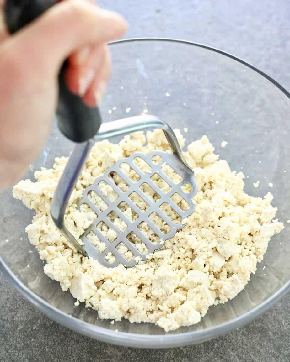 Mashing tofu in a bowl
