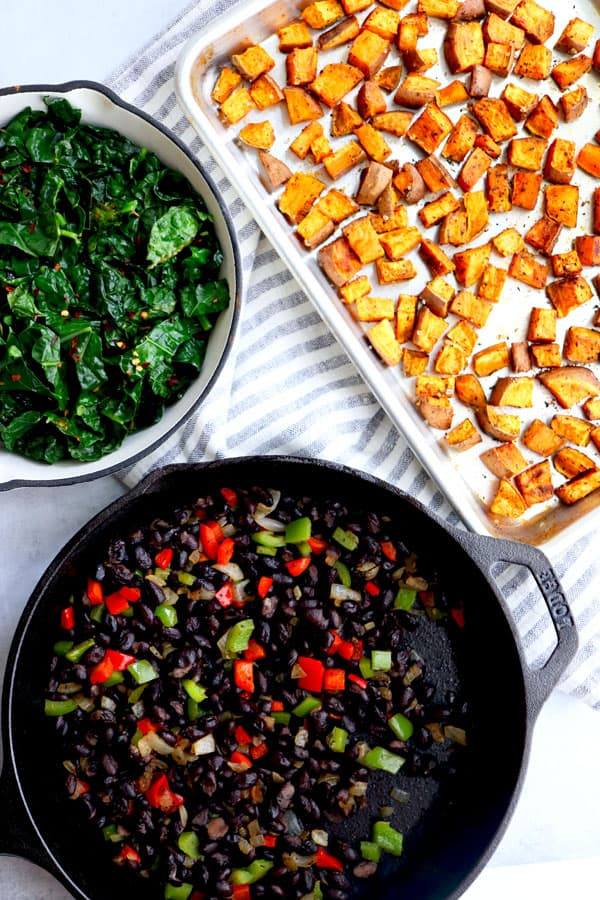 Cooked black beans in a cast iron pan next to roasted sweet potatoes and sautéed greens
