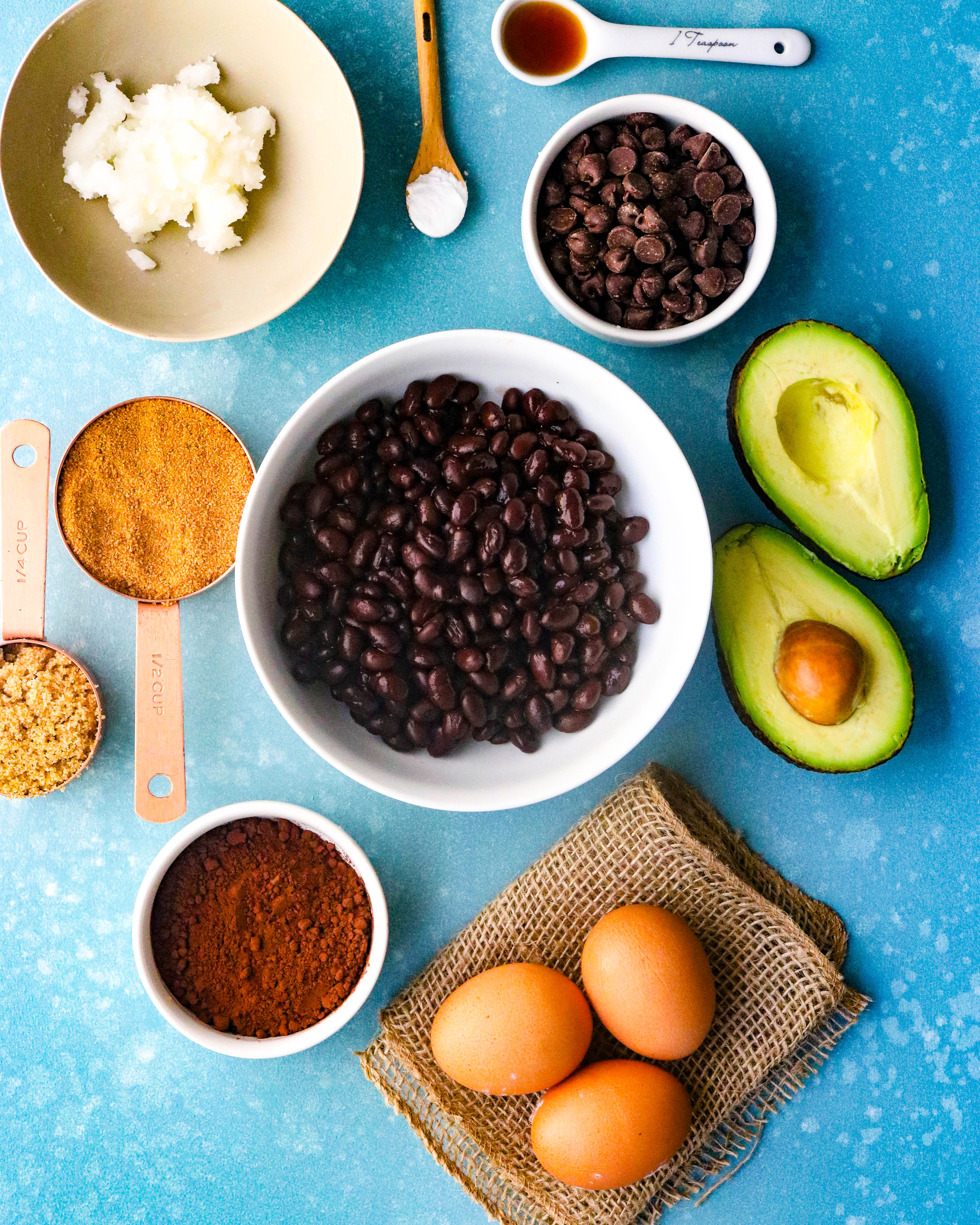 black beans, avocado, eggs, oil, and chocolate chips in bowls on a blue surface