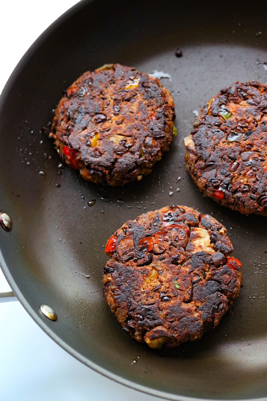 3 black bean burgers cooking in s black skillet