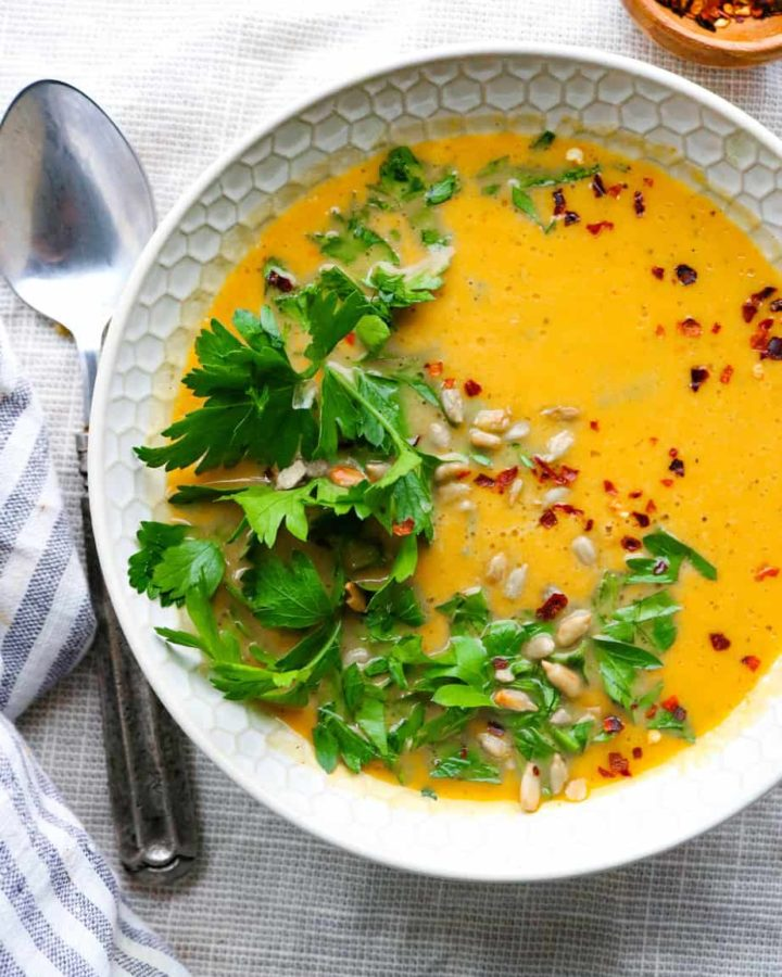 Bowl of roasted butternut squash soup topped with parsley and red pepper flakes