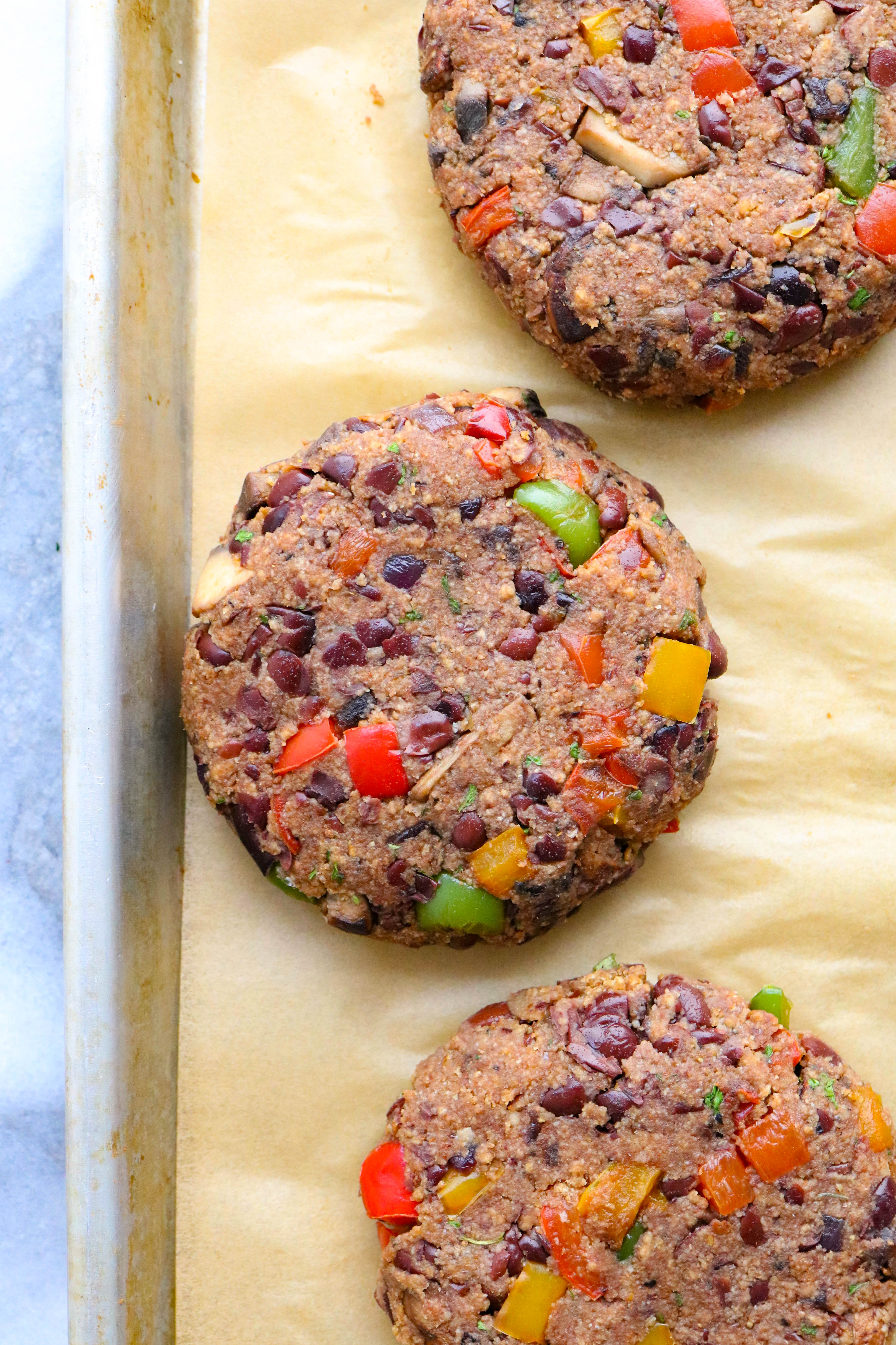 Raw veggie burger patties formed and laying onto of brown parchment paper on a baking sheet