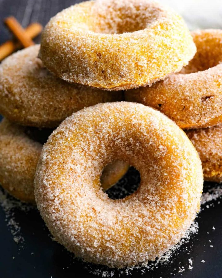Single pumpkin donut covered in cinnamon sugar with more behind it