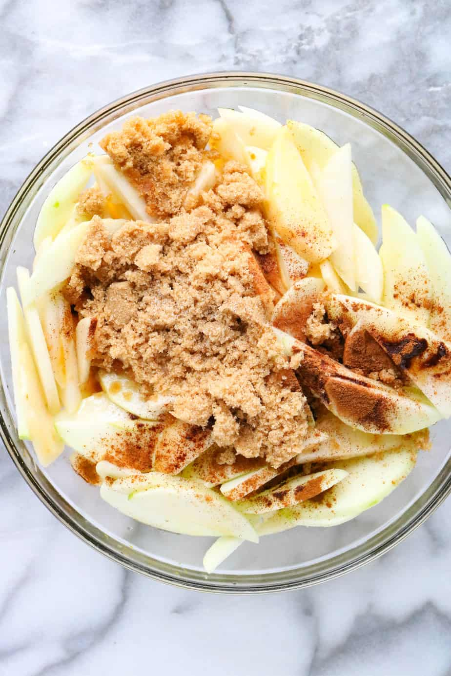 Apples and pear slices in a bowl topped with brown sugar and cinnamon