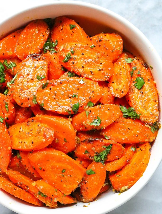 sliced carrots in a round white bowl with chopped herbs sprinkled on top