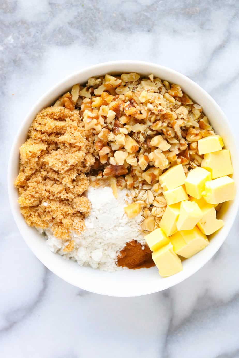 Nut and oat crumble topping ingredients in a white bowl