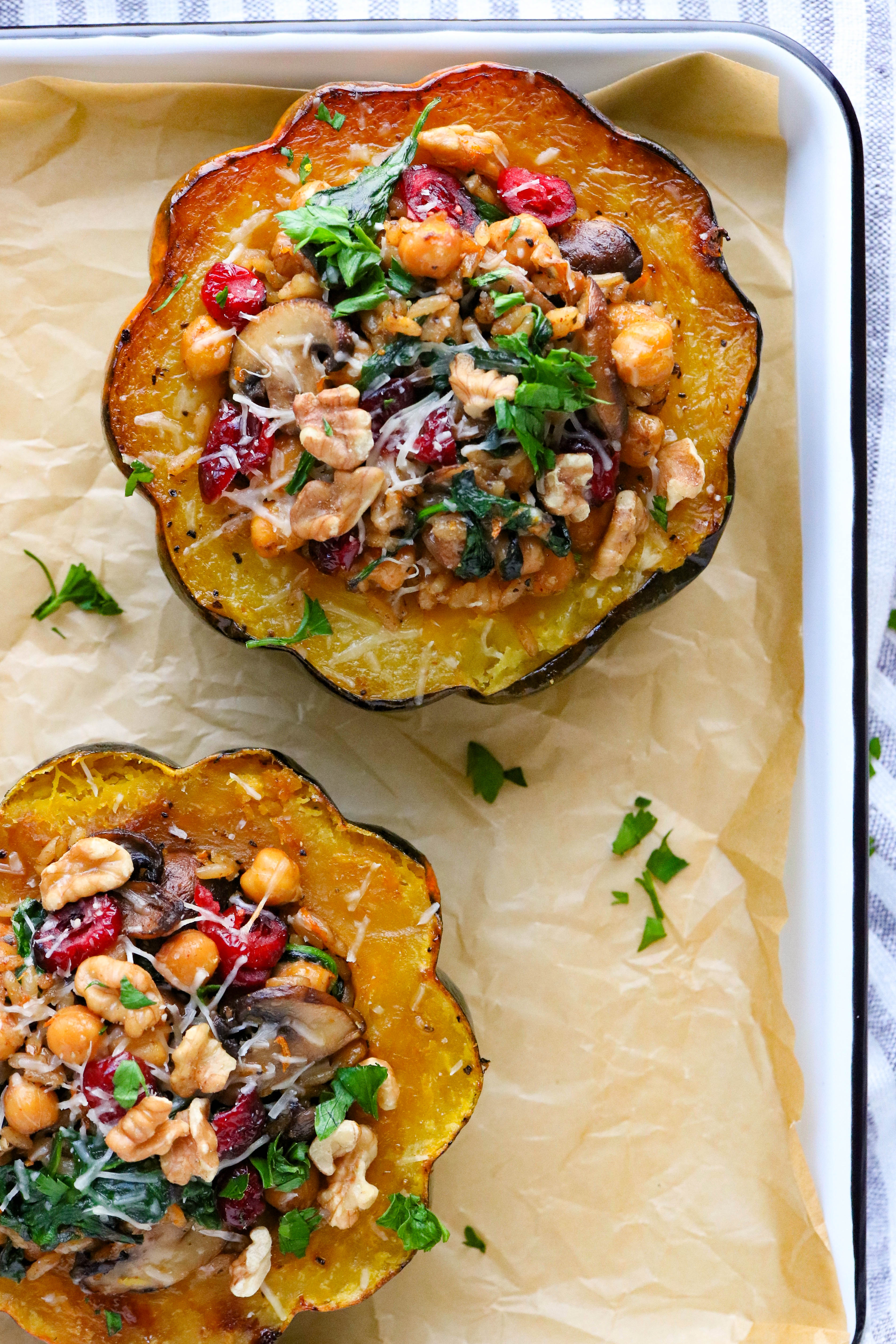 2 roasted vegetarian stuffed acorn squash on a sheet pan with brown parchment paper