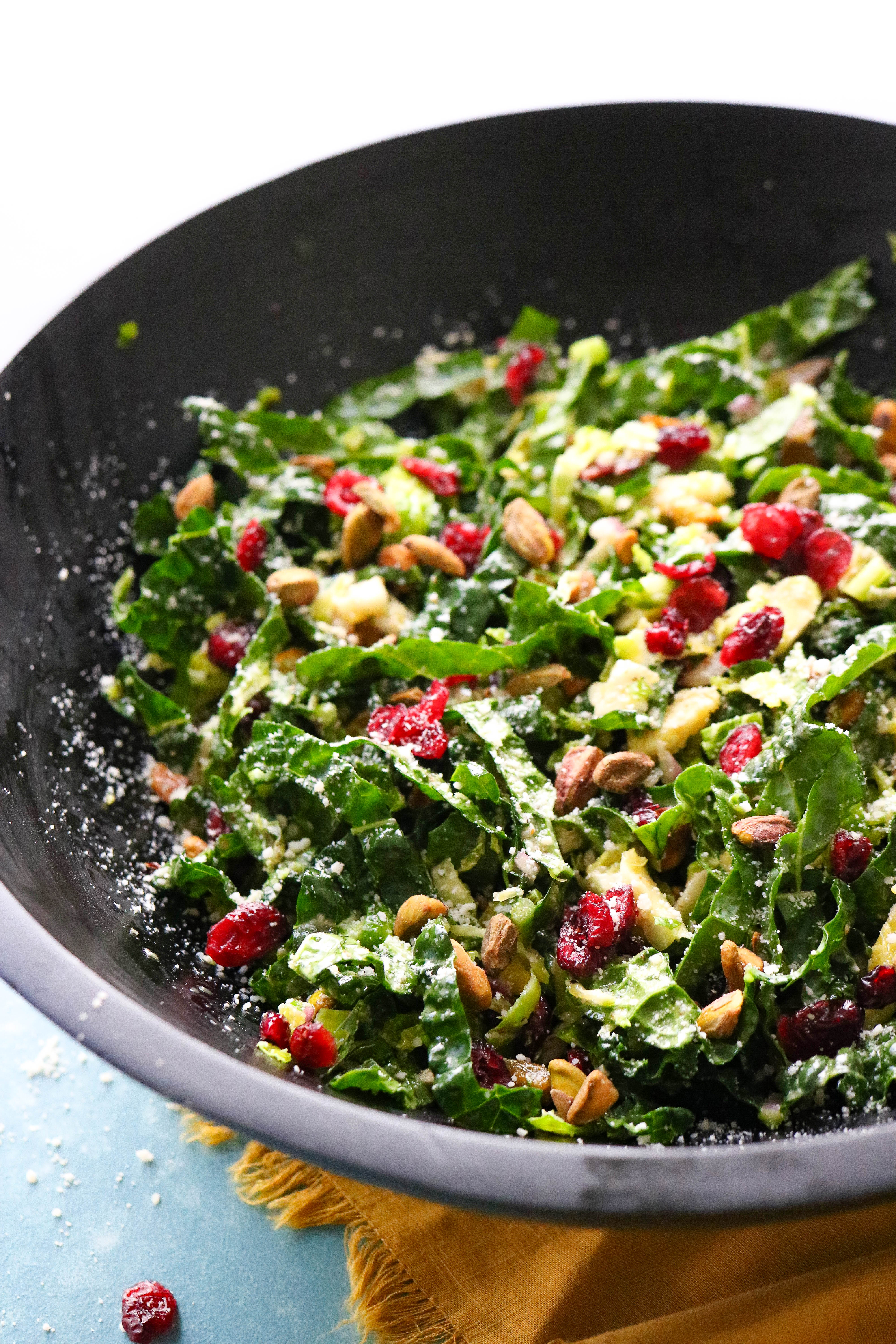 Dark round salad bowl filled with shredded kale snd Brussel sprout salad with dried cranberries and pistachios sprinkled in.
