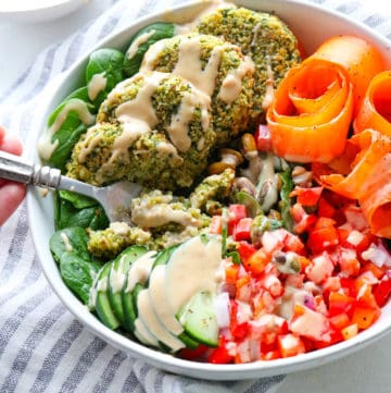 Healthy baked falafel in a bowl surrounded by veggies covered in tahini dressing