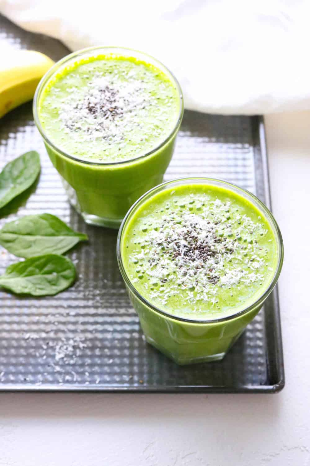 Green smoothie in two glasses on a metal tray with a banana next to it