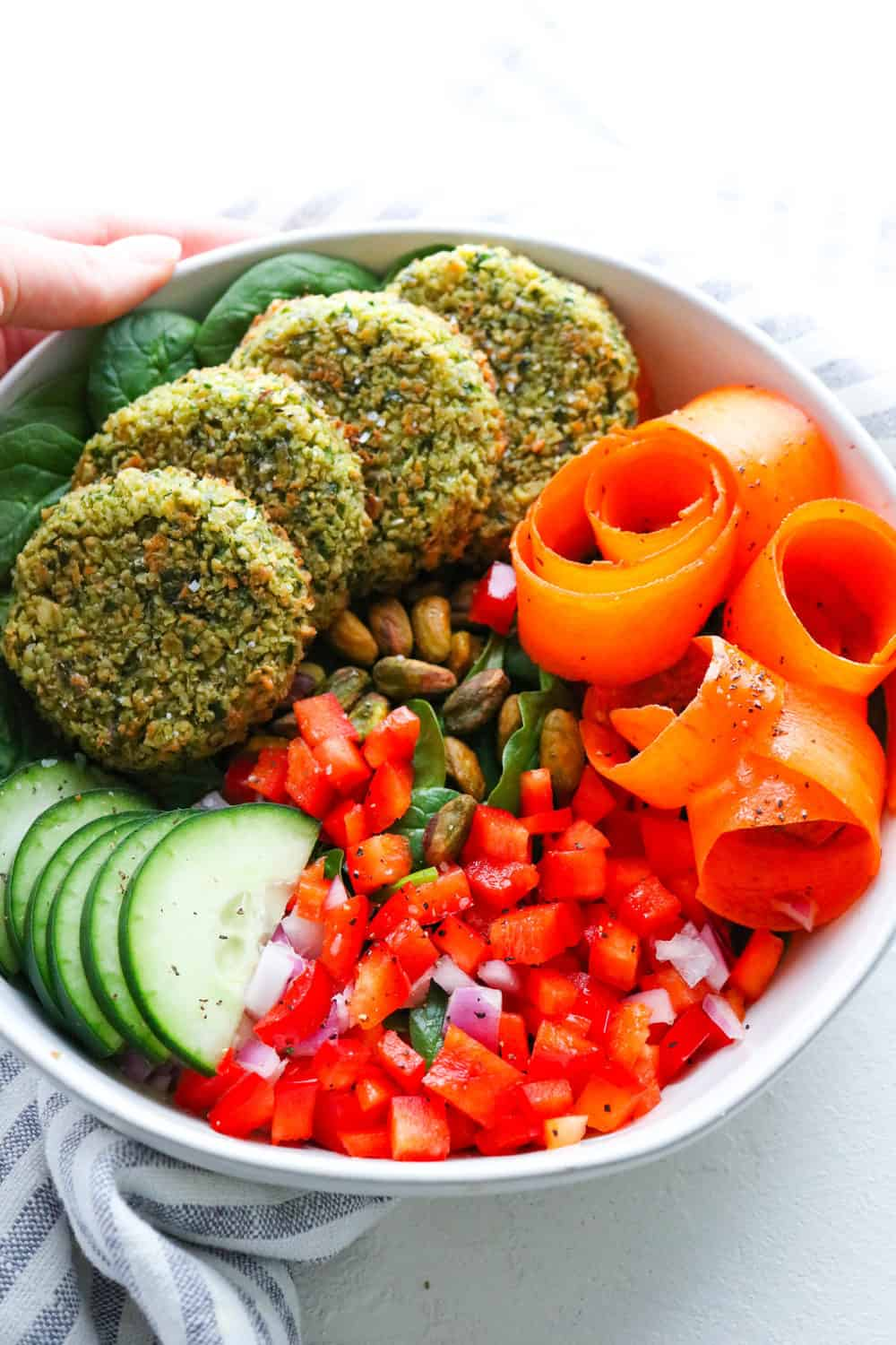 Baked falafel buddha bowl with veggies with dressing next it