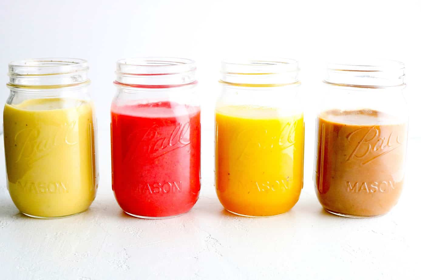 Row of four different color salad dressings in mason jars.