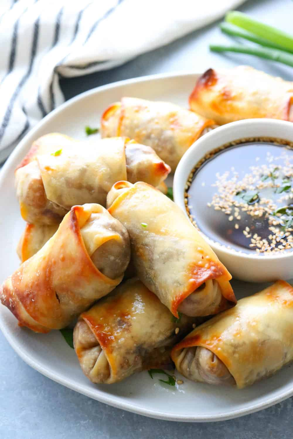 baked egg rolls piled on a plate_