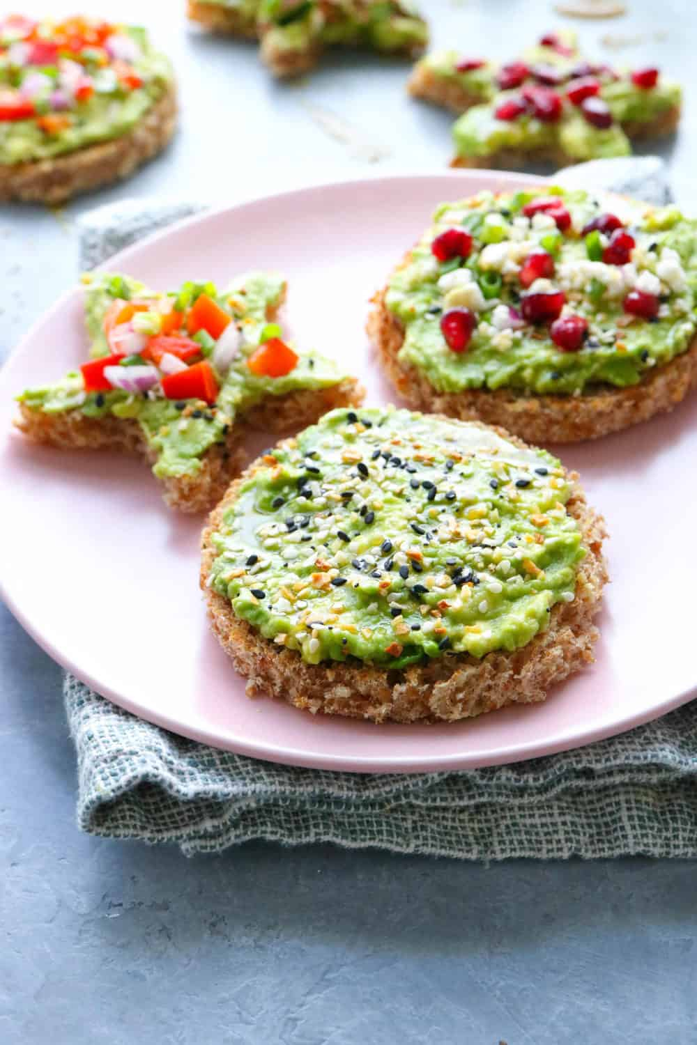 round toast on a pink plate covered in avocado topped with seeds with more behind it