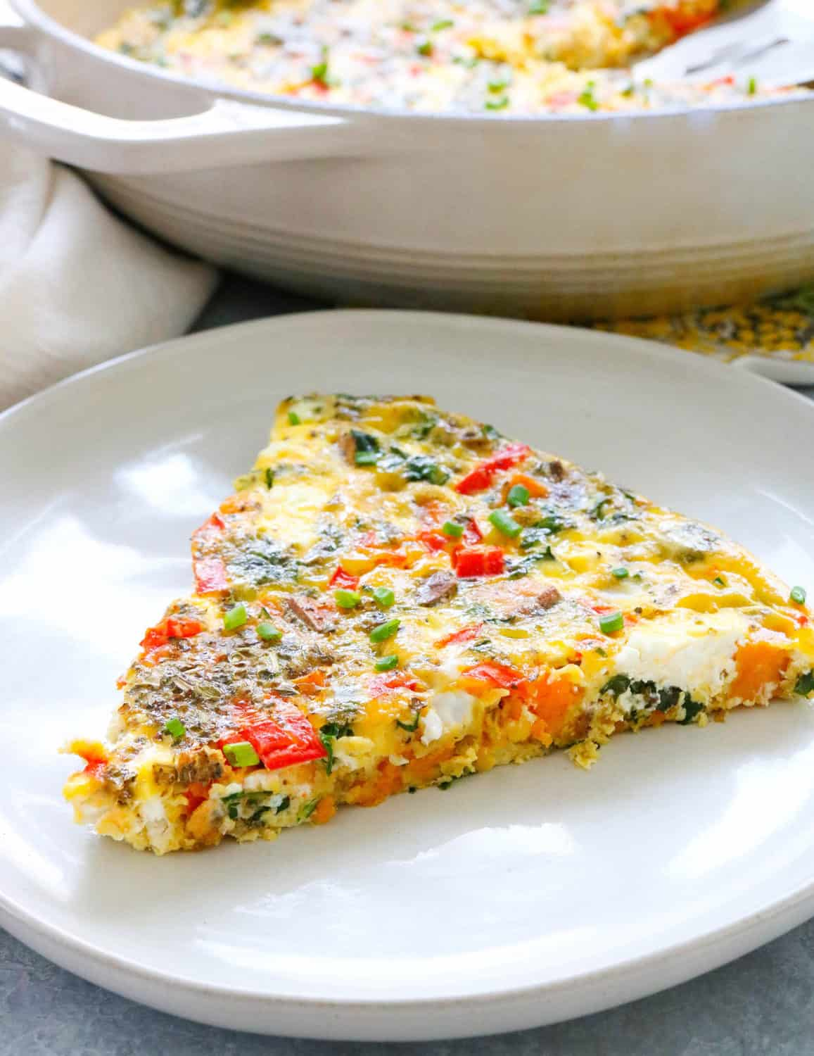 close up of piece of frittata filled with veggies and cheese on a plate