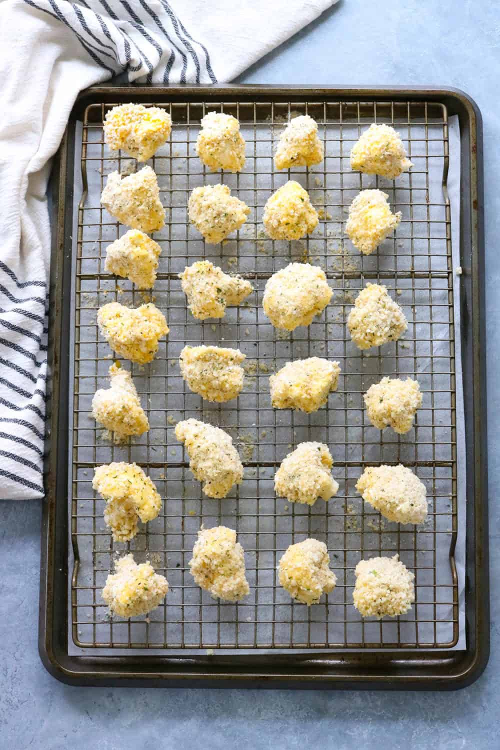 coated cauliflower on a wire racked baking sheet