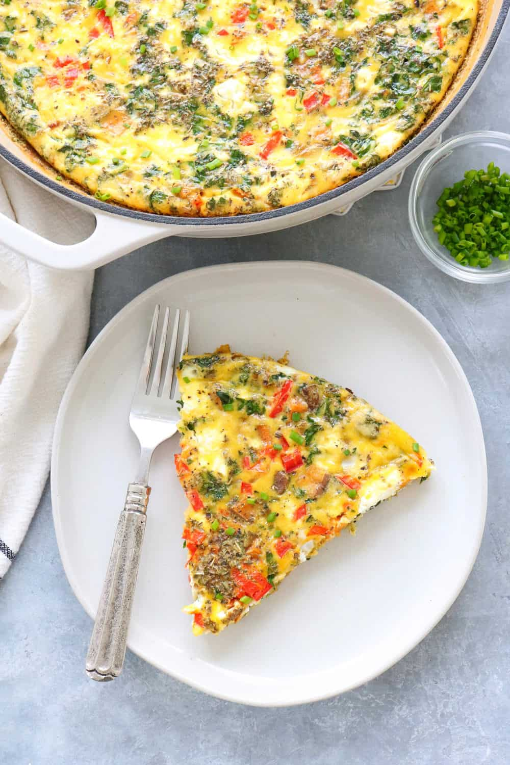 pan with vegetable frittata with a plate with a piece on top of it