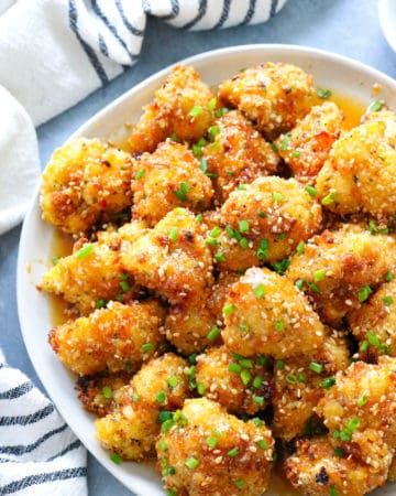 plate of sweet and spicy baked cauliflower wings toppe with diced chives and sesame seeds