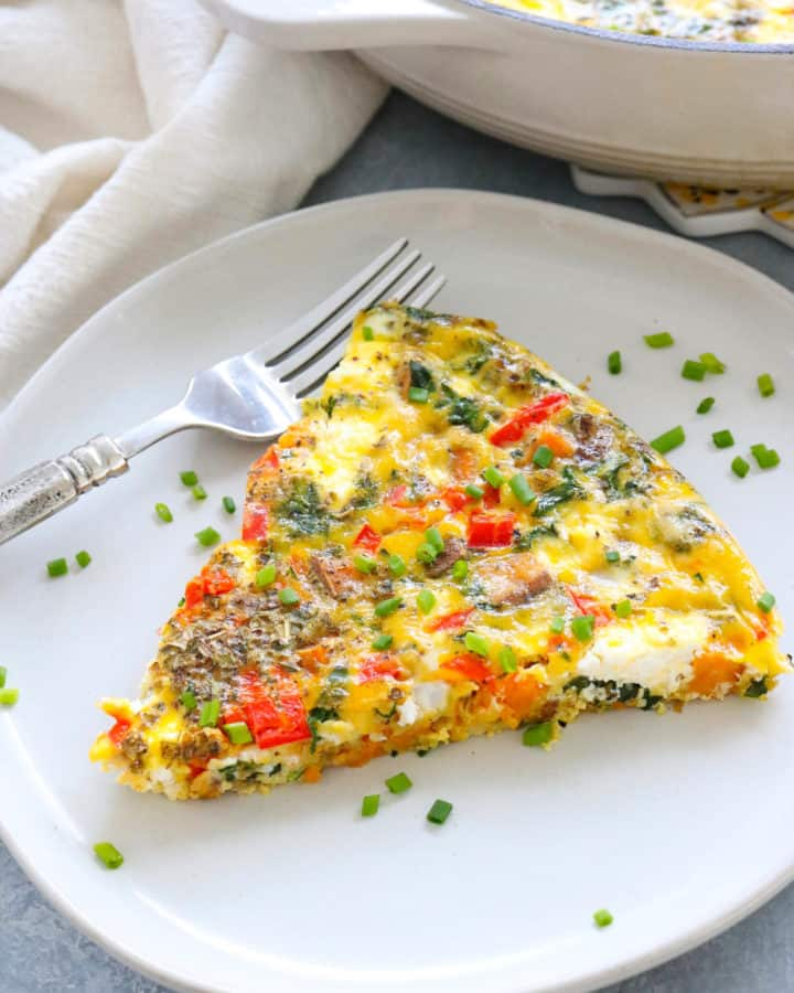 veggie frittata slie on a plate with a silver fork next to it