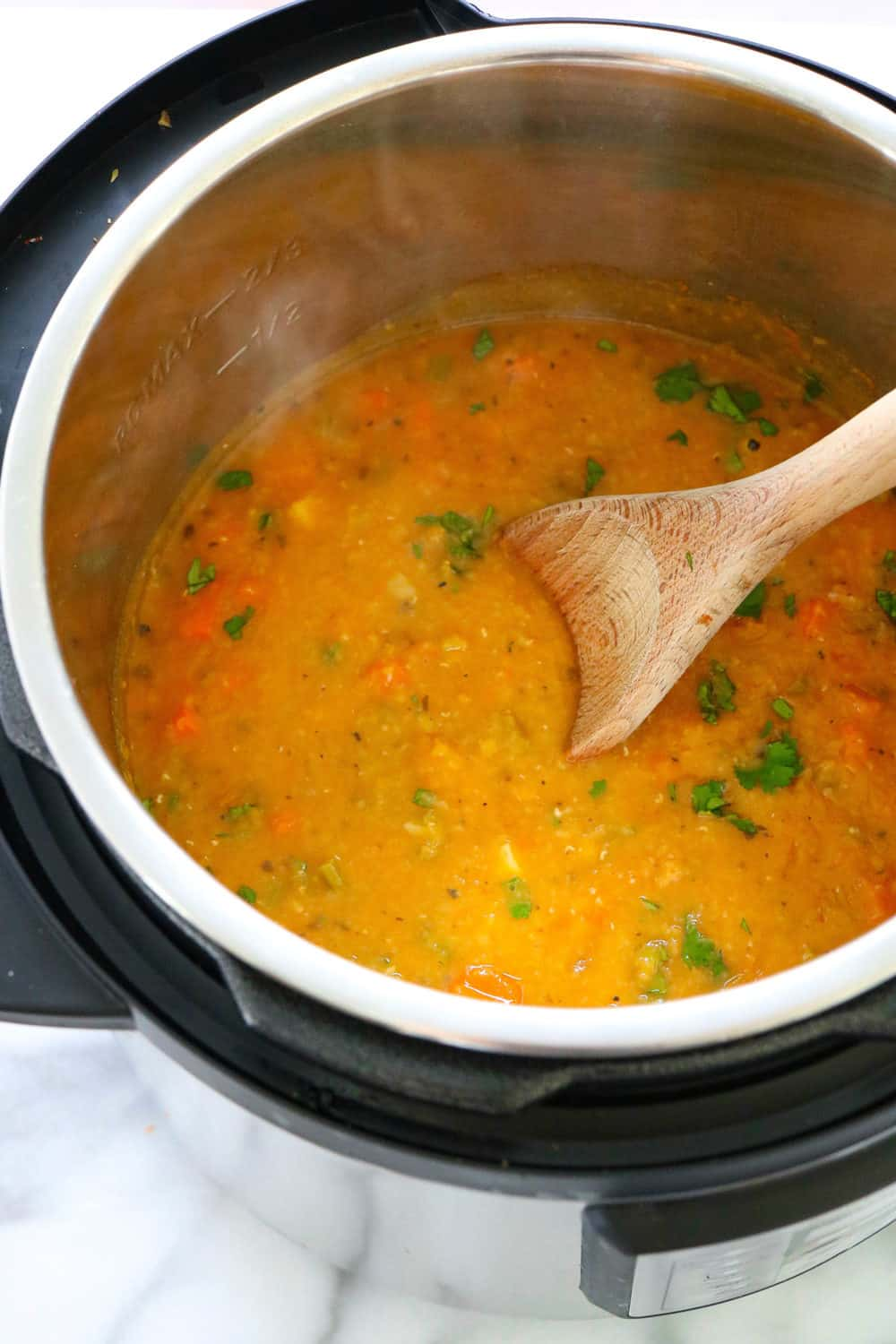 lentil soup cooking in the instant pot with a wooden spoon in it