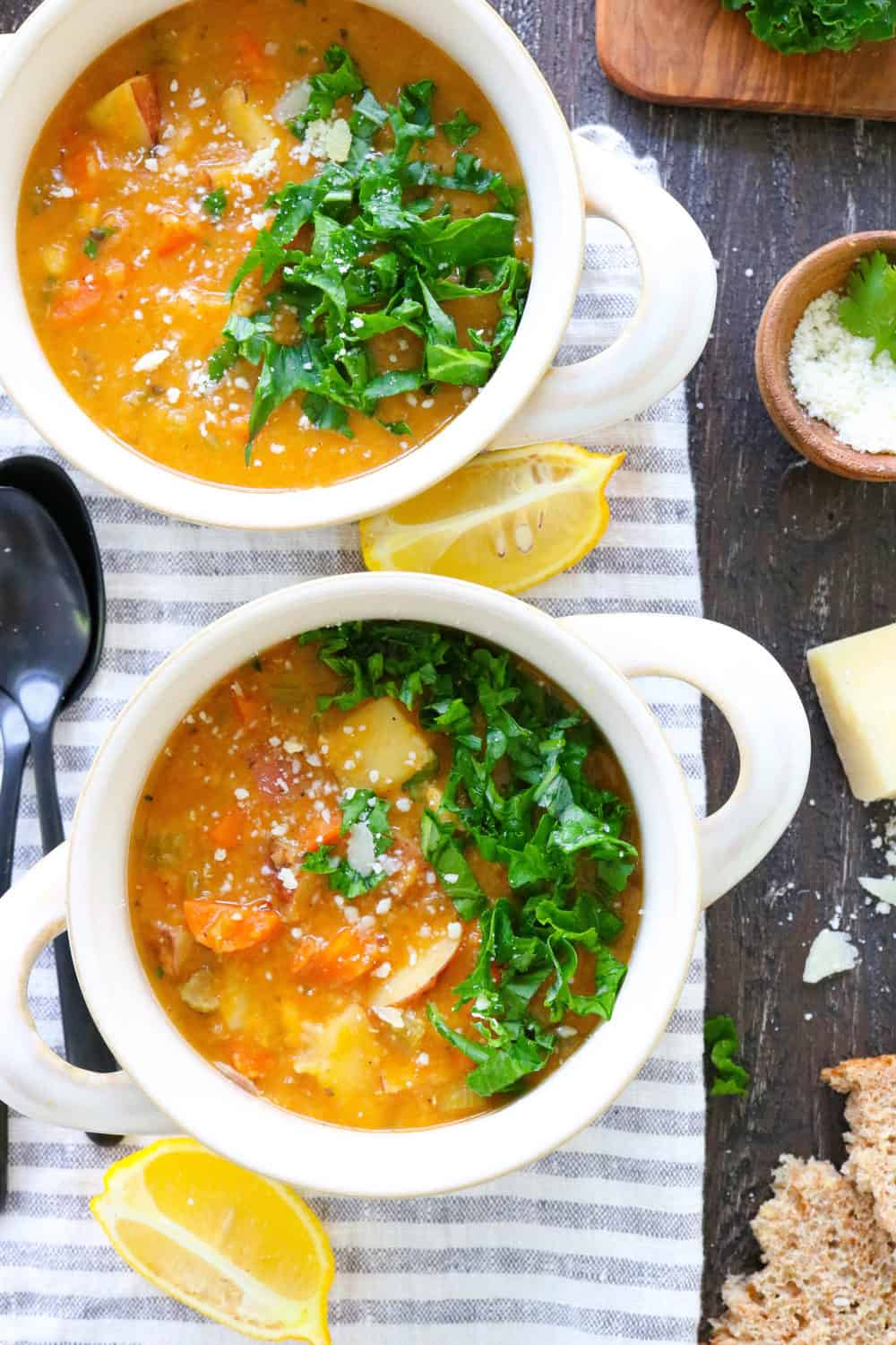 two bowls of lentil soup with kale and lemons next to them