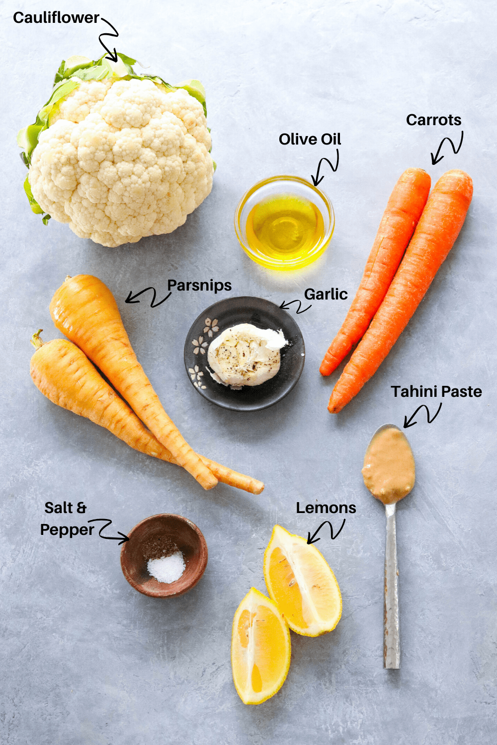 cauliflower, carrots, parsnips, lemon and tahini paste on a gray board with  labels