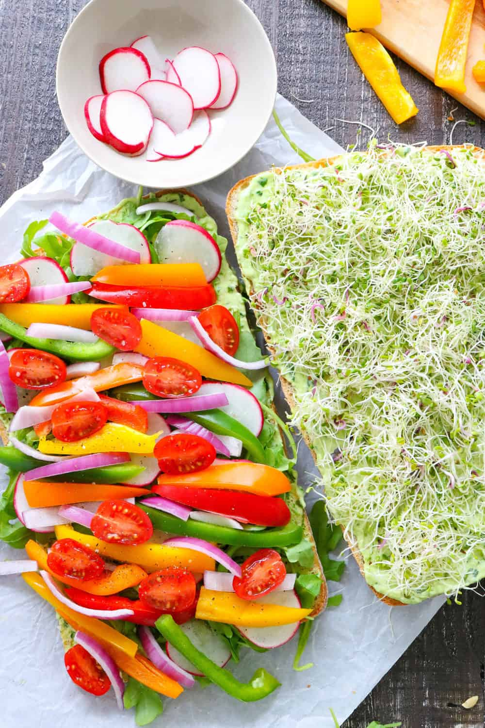 two pieces of bread with on layered with sliced peppers and onions and the other with reamy green dressing and sprouts
