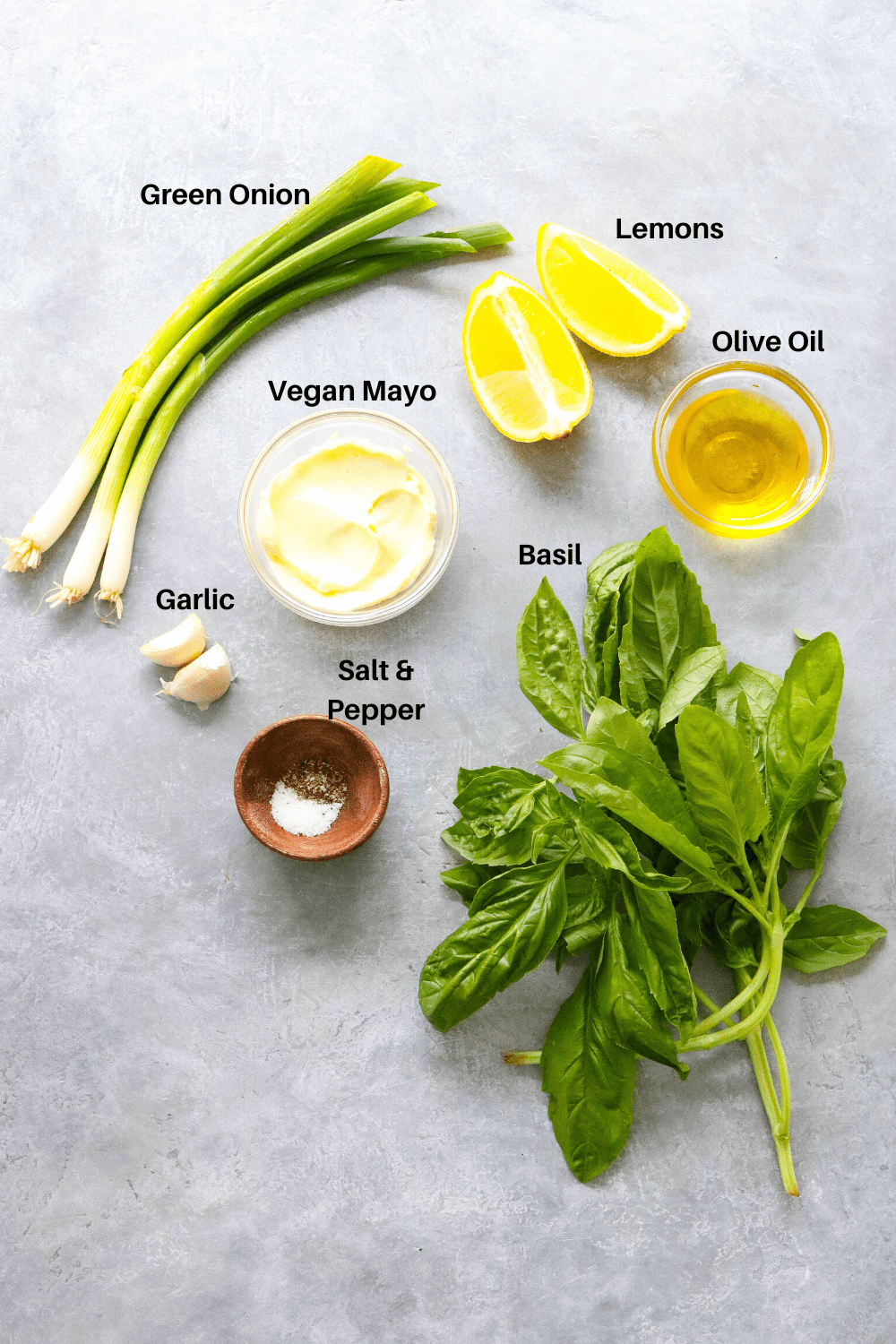 basil, green onion, lemon, mayo, and olive oil on a gray surface