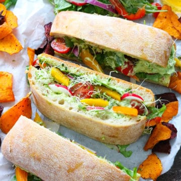 Slices of veggies sandwhich ontop of white parchment paper with yellow and red chips surrounding it