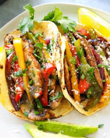 fajita veggies piled into charred corn tortillas with lime wedges next to it