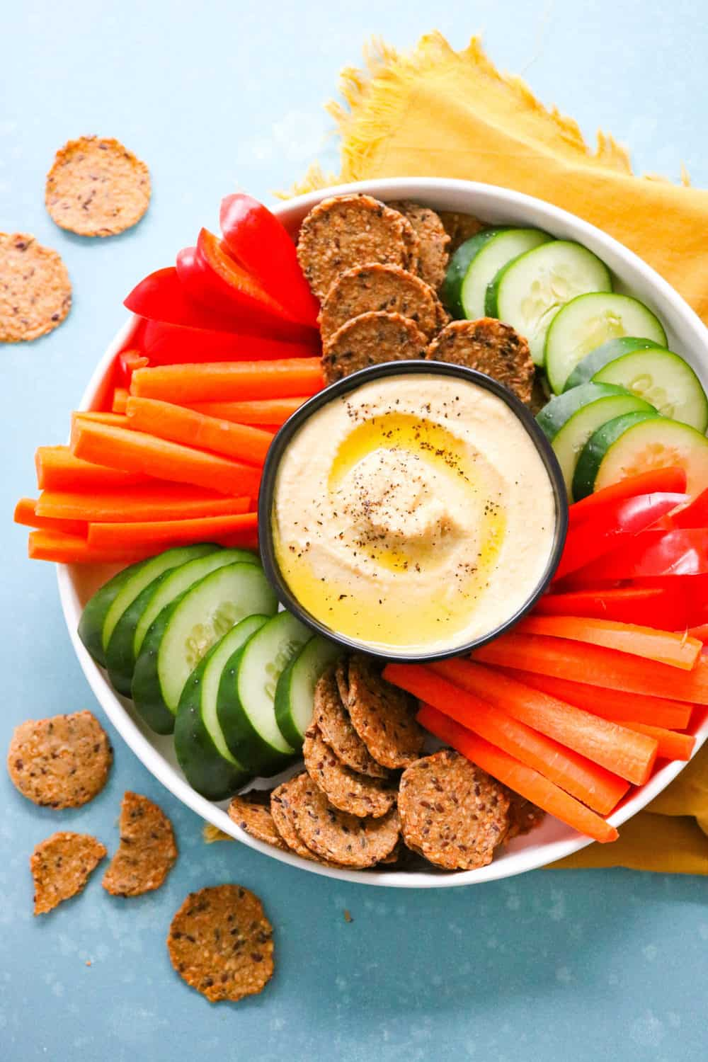 platter of classic homemade hummus with carrots and other veggies plus crackers around it