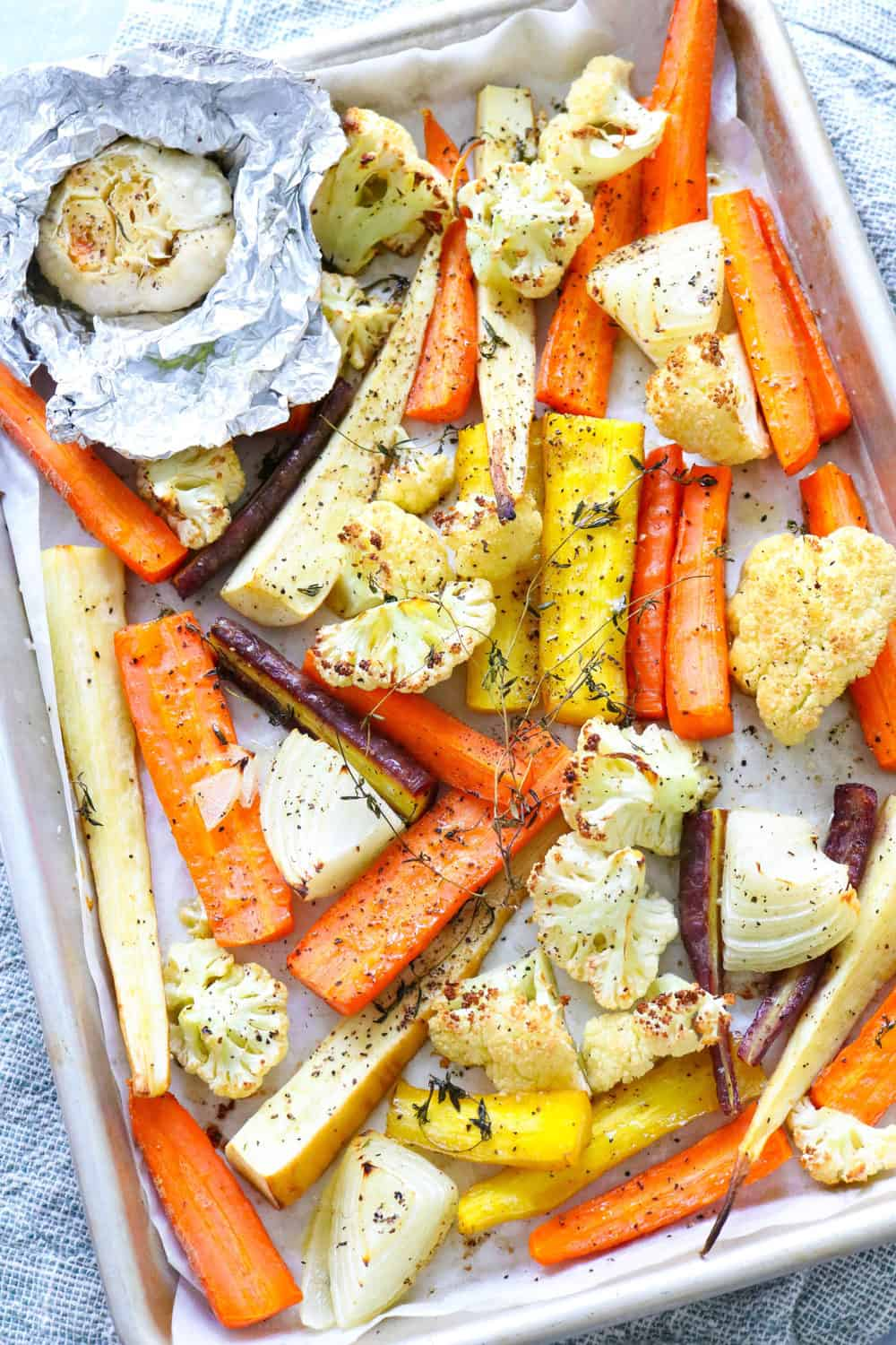 roasted carrots and parsnips on a pan with a head of garlic
