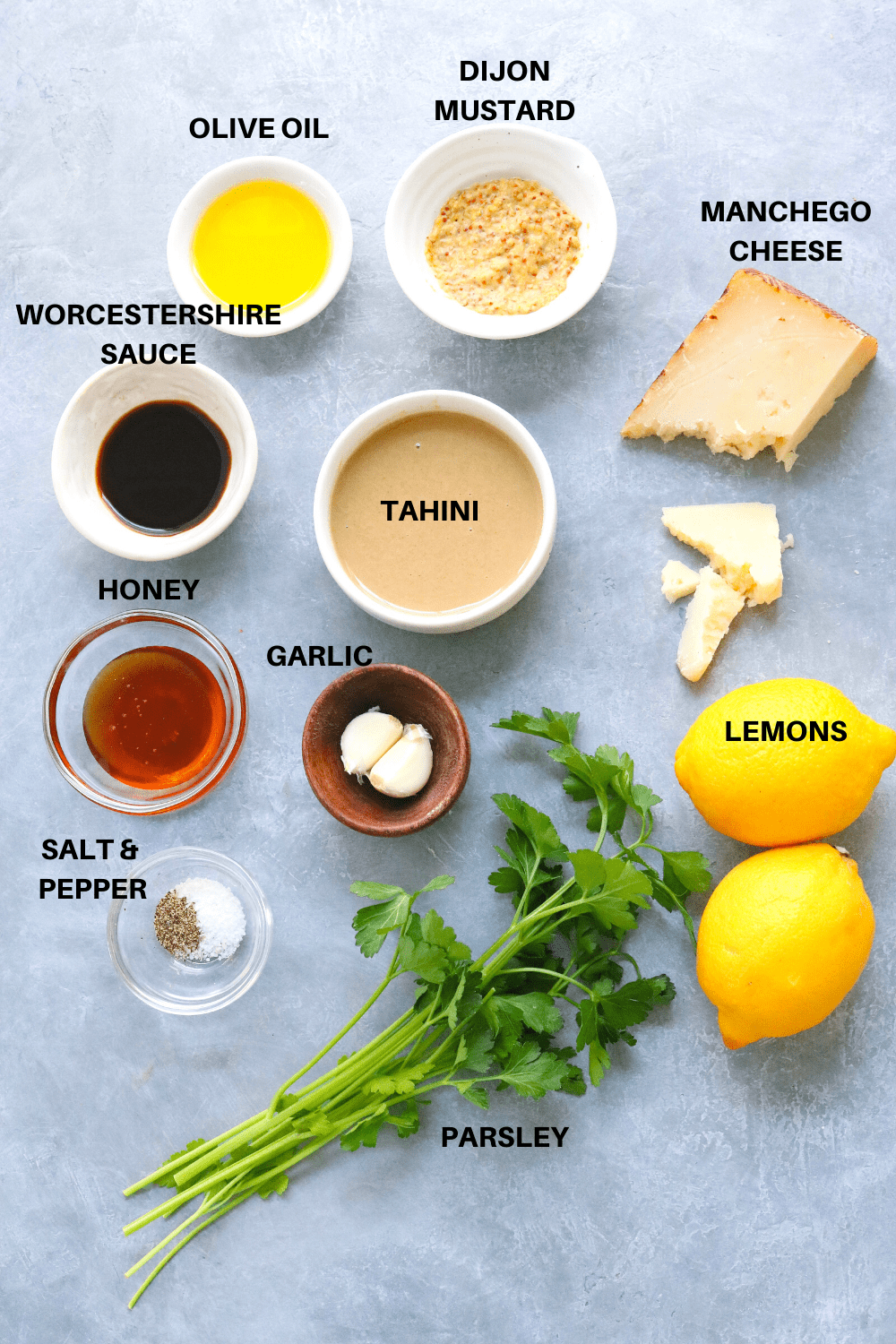 olive oil, cheese, mustard and herbs on a gray board