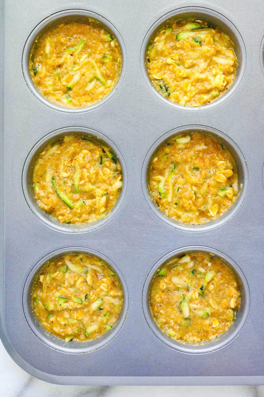Zucchini muffin batter in a muffin pan
