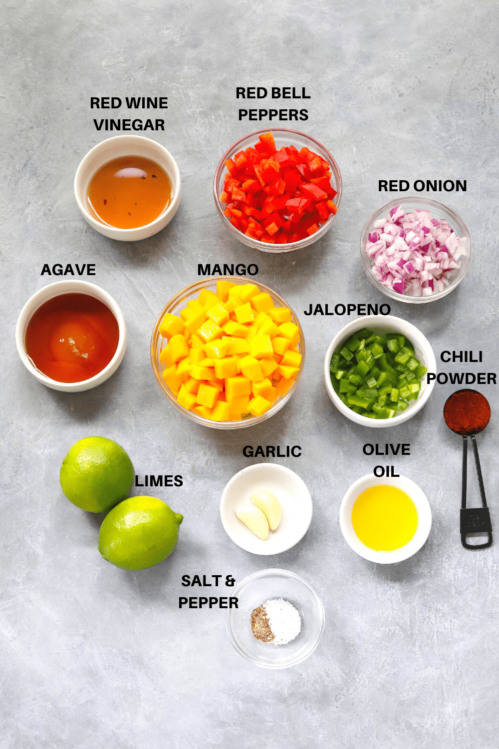 Diced mangoes, red bell peppers, red onion, jalopeno and other salsa ingredients on a gray board