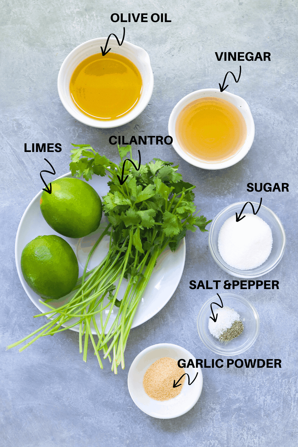 Cilantro and limes with oil and vinegar in bowls on a gray board