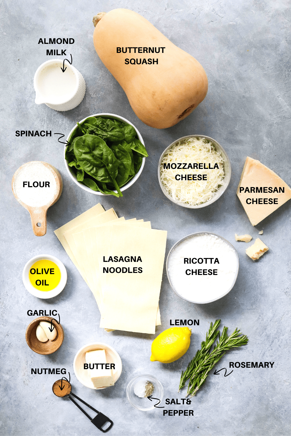 Whole butternut squash, white cup of milk, bowl of spinach, bowl of shredded mozzarella cheese, cup of flour, lasagna noodles, ricotta cheese, lemon and herbs all laid out on a gray surface.