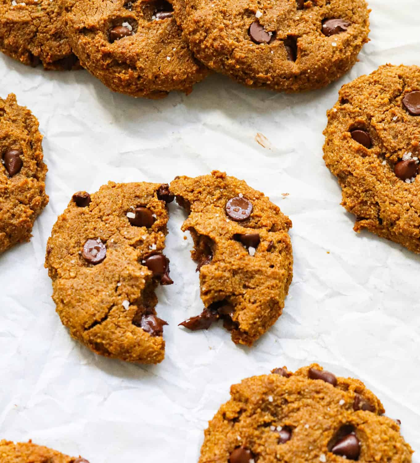 Broken chocolate chip cookies with more around it