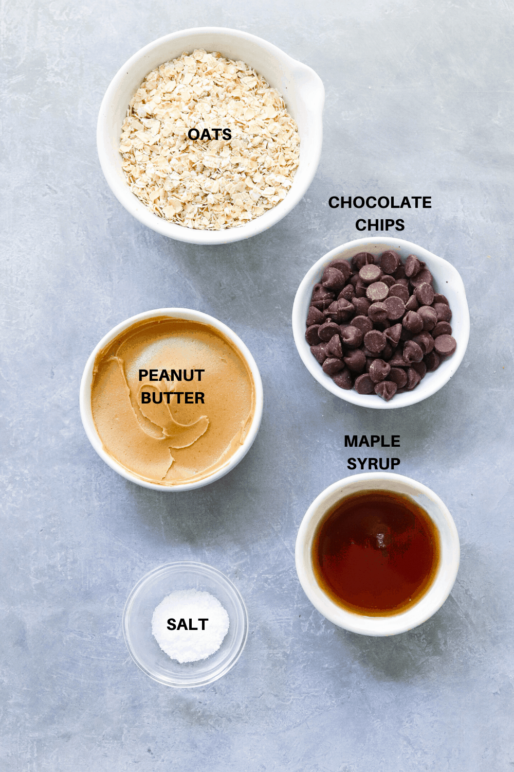 Oats, peanut butter and chocolate chips in bowls on a gray board.